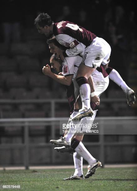 Northampton Town's Bradley Johnson celebrates scoring their fourth goal against Bournemouth with Daniel Jones and Mark Hughes