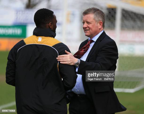 Northampton Town's manager Chris Wilder talks to one of his coaching staff before the game against Mansfield Town