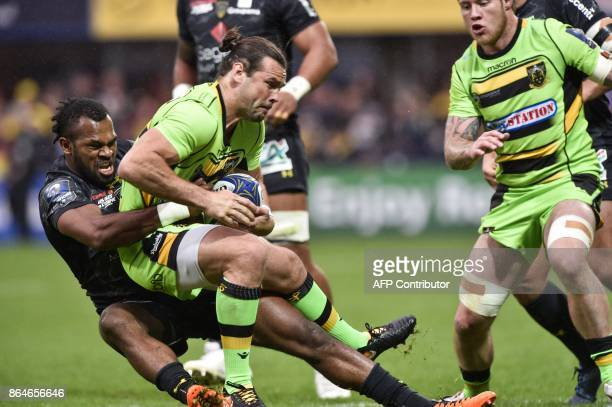 Northampton's scrumhalf Ben Foden is tackled by Clermont's Fijian wing Alivereti Raka during the European Rugby Champions Cup match ASM Clermont...