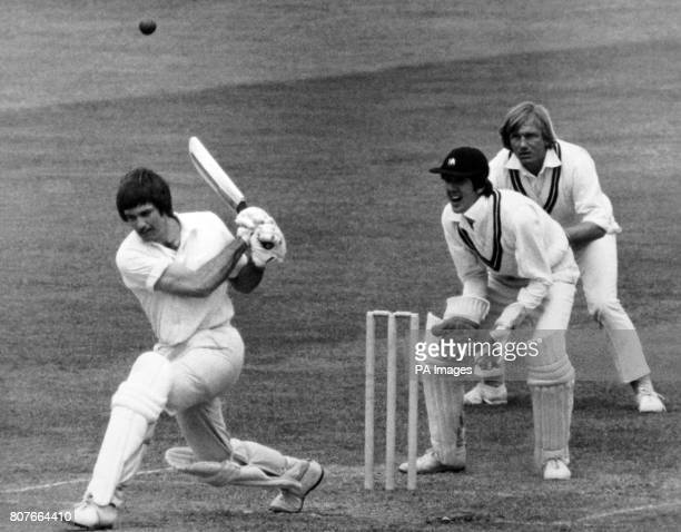 Northamptonshire batsman Peter Willey in action with Middlesex wicketkeeper George Sharp poised for a catch