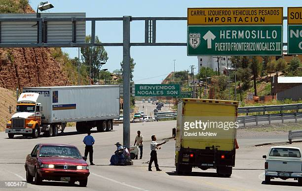 A northbound truck left crosses the border to enter the United States from Nogales Sonora Mexico August 1 2001 near Nogales AZ In defiance of veto...