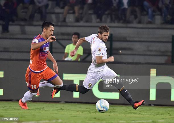 Northeast United FC's forward Emiliano Alfaro vies for the ball with FC Pune Citys defender Gouramangi Singh during the Indian Super League football...