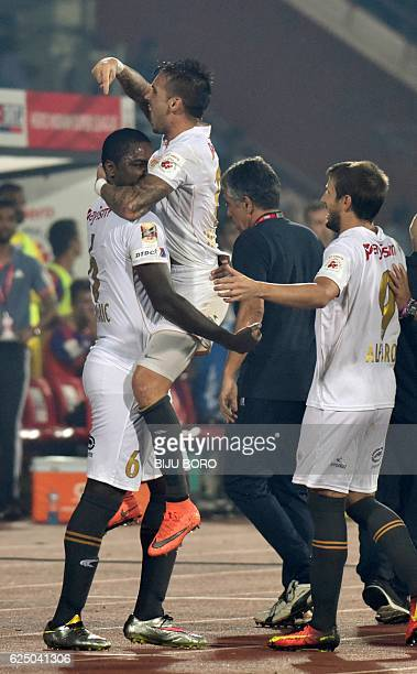 Northeast United FC's midfielder Kaffi Ndri celebrates with his teammates after scoring a goal during the Indian Super League football match between...