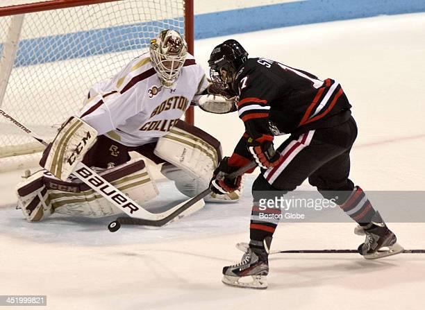 Northeastern University ice hockey player Torin Snydeman has his shot on goal denied by Boston College goalie Brian Billett during second period...