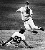 Northeastern University player Mike Langston bottom steals second base as Boston College player Tom Mandile top jumps for a high throw during a...