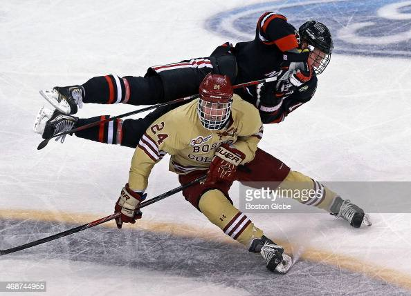 Northeastern University's John Stevens sails over Boston College's Bill Arnold during a first period mid ice collision Northeastern University and...