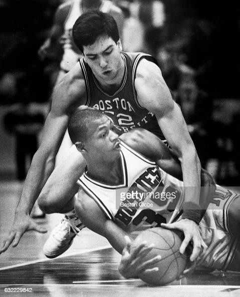 Northeastern University's Reggie Lewis grabs for a loose ball on the ground as Boston University's Peter Gabriel surrounds him from above in Boston...