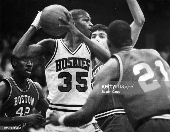 Northeastern University's Reggie Lewis is surrounded by Boston University's Larry Jones and Paul Hendricks as he tries to pass during a men's college...