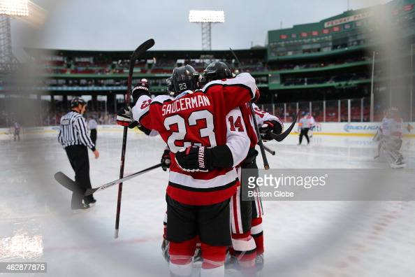 Northeastern's Colton Saucerman congratulates teammate Braden Pimm who scored a second period goal to put Northeastern University up 10 during a...