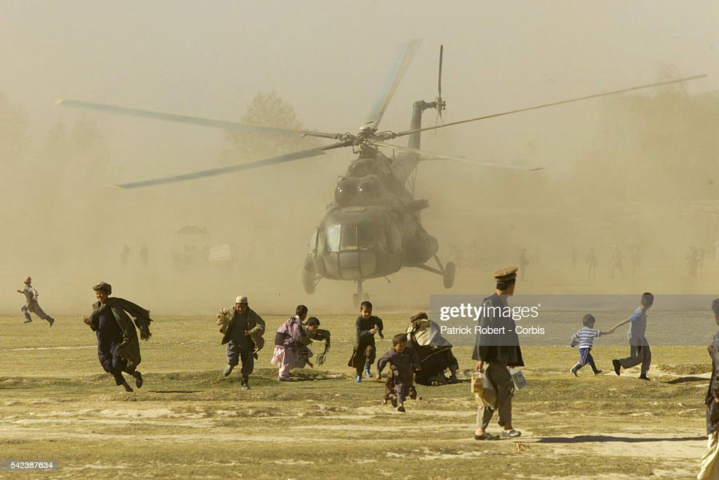 A Northern Alliance helicopter frightens inhabitants during a difficult takeoff from the Taloqan stadium