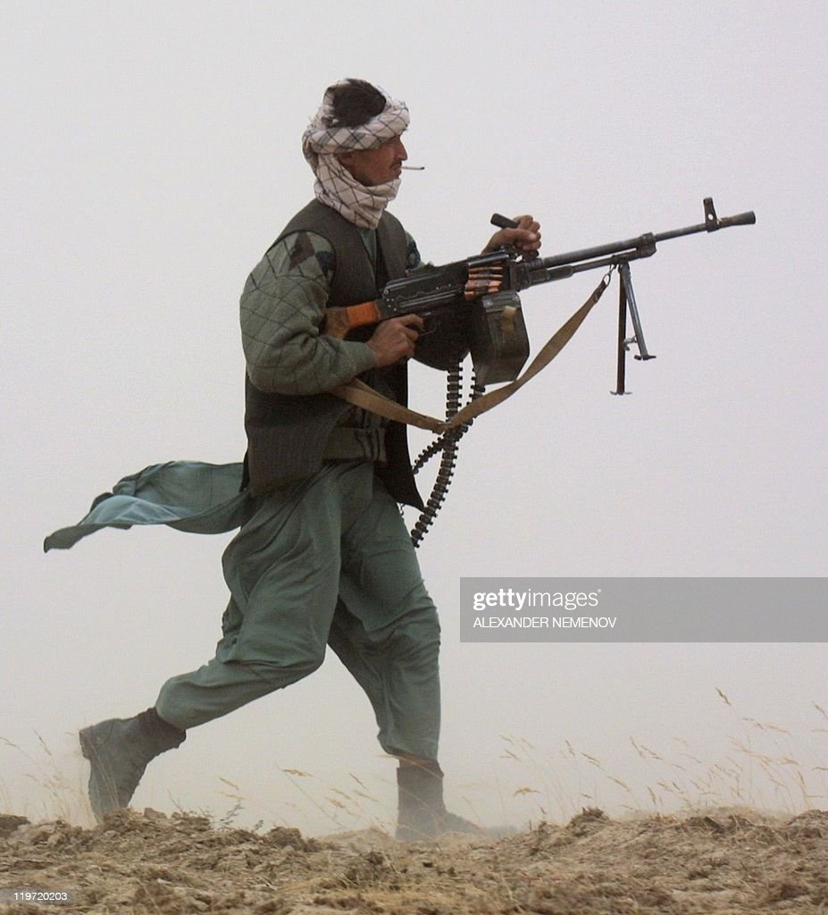 A Northern Alliance soldier fires his machinegun on his position some 700 meters from Taliban 's front line 10 October 2001 not far from the village...