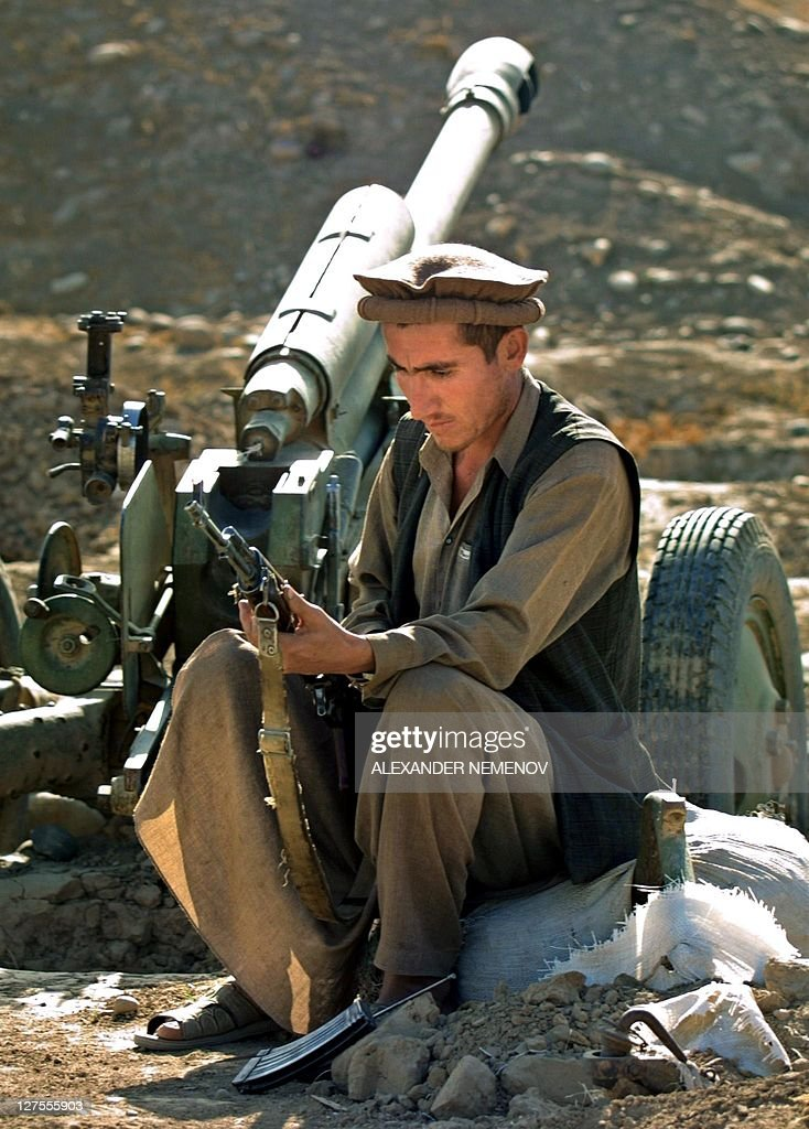 Northern Alliance soldier inspects his Kalashnikov sitting near his gun not far from the village of DashtIQala 12 October 2001 a few kilometres from...