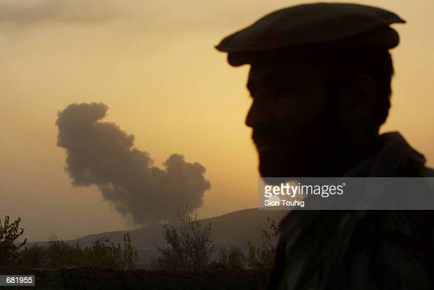 Northern Alliance soldier passes a plume of smoke caused by USled bombing during air strikes on Taliban positions November 15 2001 at the front line...