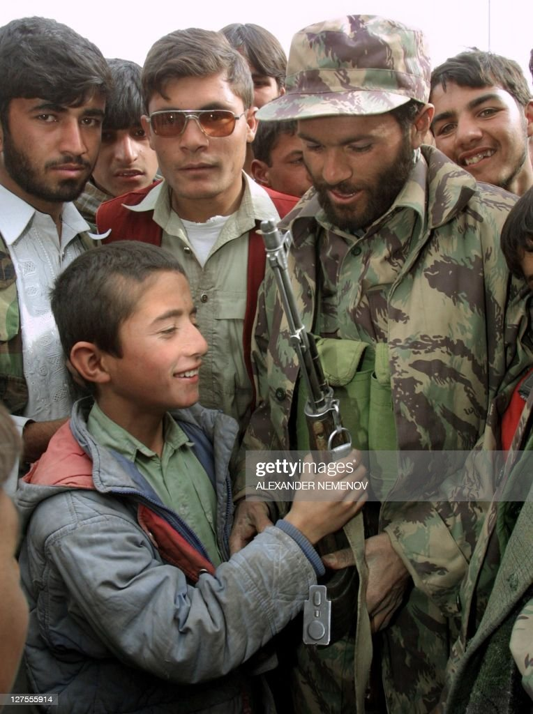 A Northern Alliance soldier shows his Kalashnikov to a local boy in Kabul 13 November 2001 after Northern Alliance captured the Aghani capital...