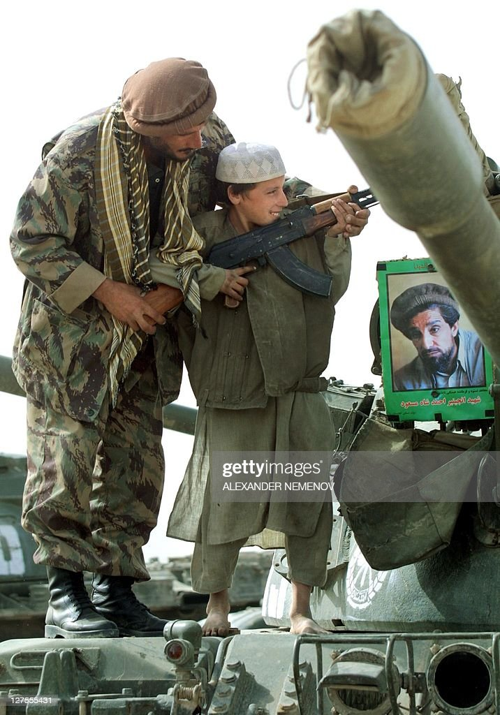 A Northern Alliance soldier teaches a young boy how to hold Kalashnikov standing on a tank of his regiment with the portrait of assassinated Afghan...