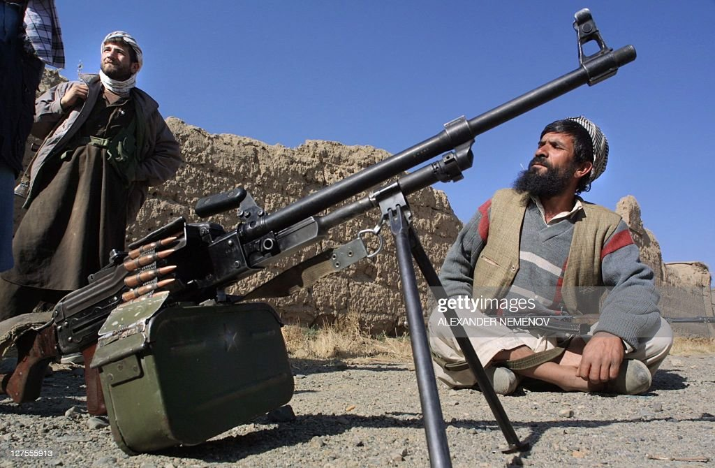 Northern Alliance soldiers discuss in front of a Kalashnikov machinegun 11 November 2001 in the village of Bagram some 25 kms north from Kabul where...
