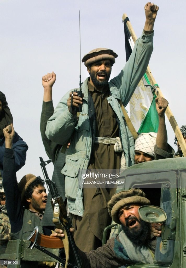 Northern Alliance soldiers shout 'Allah Akbar' and salute as they drive into Kabul 13 November 2001 after they captured the Afghani capital...