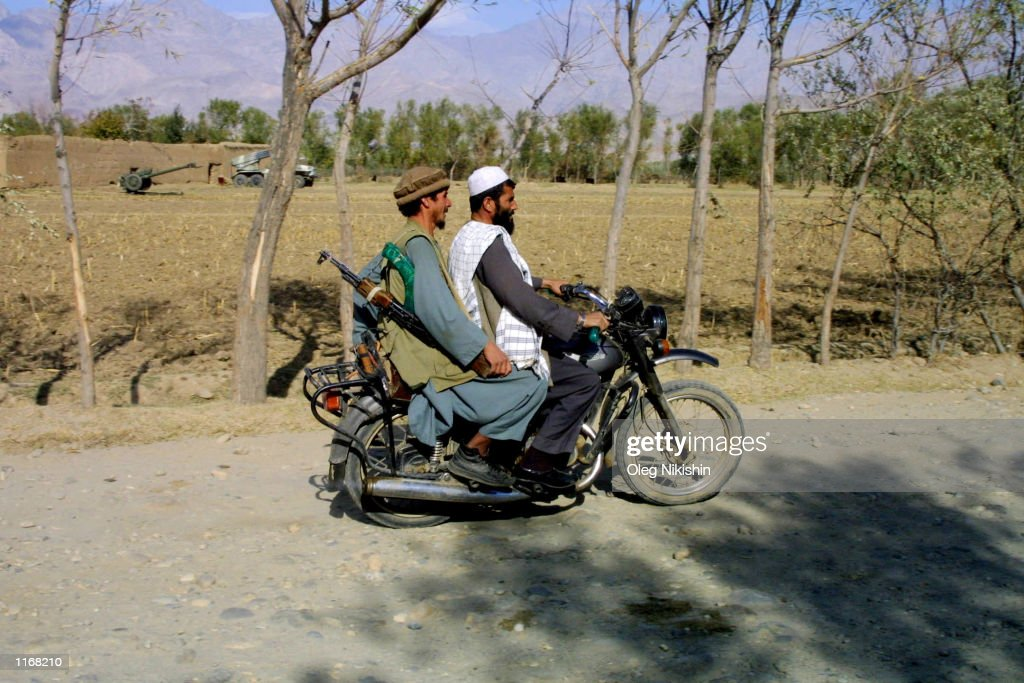 Northern Alliance soldiers travel on a motorcycle in the village of Shokhi 8 miles from the front line October 17 2001 in Northern Afghanistan