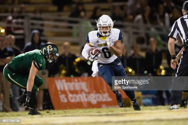 Northern Arizona Lumberjacks running back Cory Young runs through a hole in the Cal Poly Mustangs line during the game between the Northern Arizona...