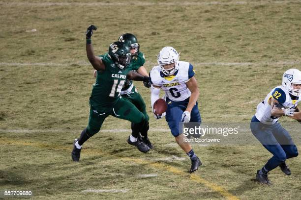 Northern Arizona Lumberjacks running back Cory Young runs to the outside with Cal Poly Mustangs defensive back Darren Adjei going for the tackle...