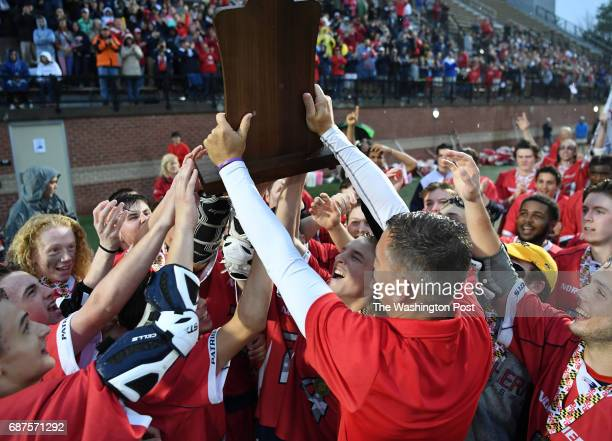Northern head coach Joe Casalino hoists the championship trophy after their victory over Glenelg during the Maryland State 3A/2A lacrosse...