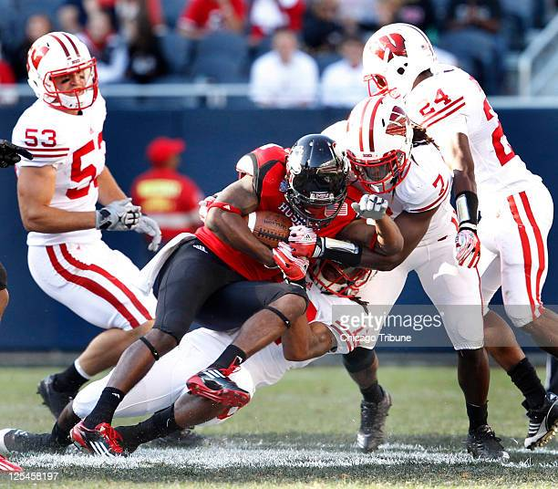 Northern Illinois wide receiver Da'Ron Brown is brought down by Wisconsin defensive back Dezmen Southward with assistance from teammate safety Aaron...