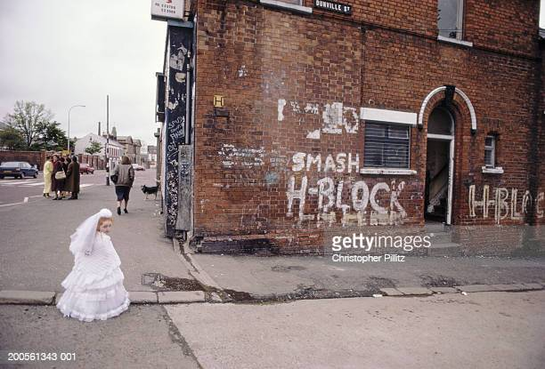 Northern Ireland, Belfast, girl in holy communion dress in street
