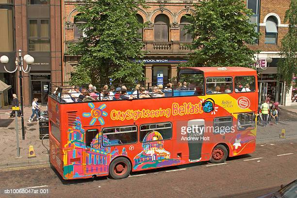 UK, Northern Ireland, City of Belfast, Tourist in open top double-decker bus on street