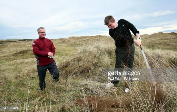 Northern Ireland Environment minister Alex Attwood watches Irish under 14 team member Owen Crooks aged 13 play golf on the site of the proposed new...