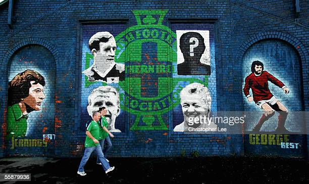 Northern Ireland fans walk past a tribute to past Northern Ireland Legends on their way to the game during the FIFA World Cup Qualifier Group Six...