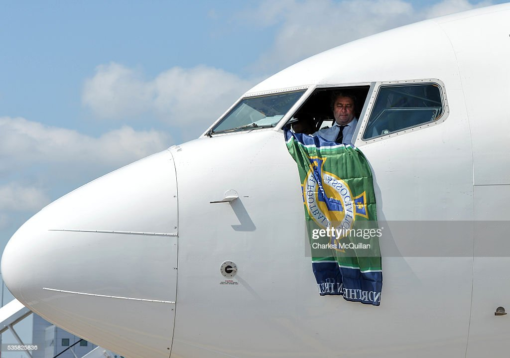 A Northern Ireland flag is unfurled from the cockpit window before the Northern Ireland teams training camp departure at George Best City Airport on May 30, 2016 in Belfast, Northern Ireland. Northern Ireland have qualified for the Euro 2016 football championship finals in France, the first time the province has qualified for an international football tournament final since 1986.