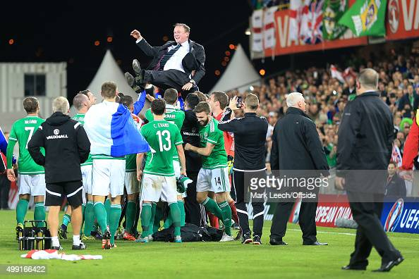 Northern Ireland manager Michael O'Neill is thrown into the air by the players as his side celebrate victory and qualification after the UEFA EURO...
