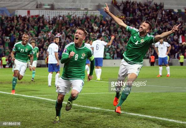 Northern Ireland midfielder Steven Davis celebrates with Northern Ireland's defender Gareth McAuley after scoring his team's third goal during the...