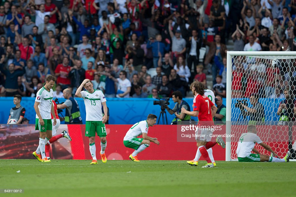 Northern Ireland players look dejected after conceding a goal to go 1-0 behind during the UEFA Euro 2016 Round of 16 match between Wales and Northern Ireland at Parc des Princes on June 25 in Paris, France.
