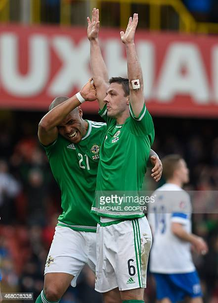 Northern Ireland's defender Chris Baird and Northern Ireland's striker Josh Magennis celebrate at the final whistle in the Euro 2016 qualifying...