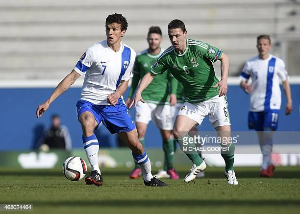 Northern Ireland's defender Chris Baird vies with Finland's midfielder Roman Eremenko during the Euro 2016 qualifying football match between Northern...
