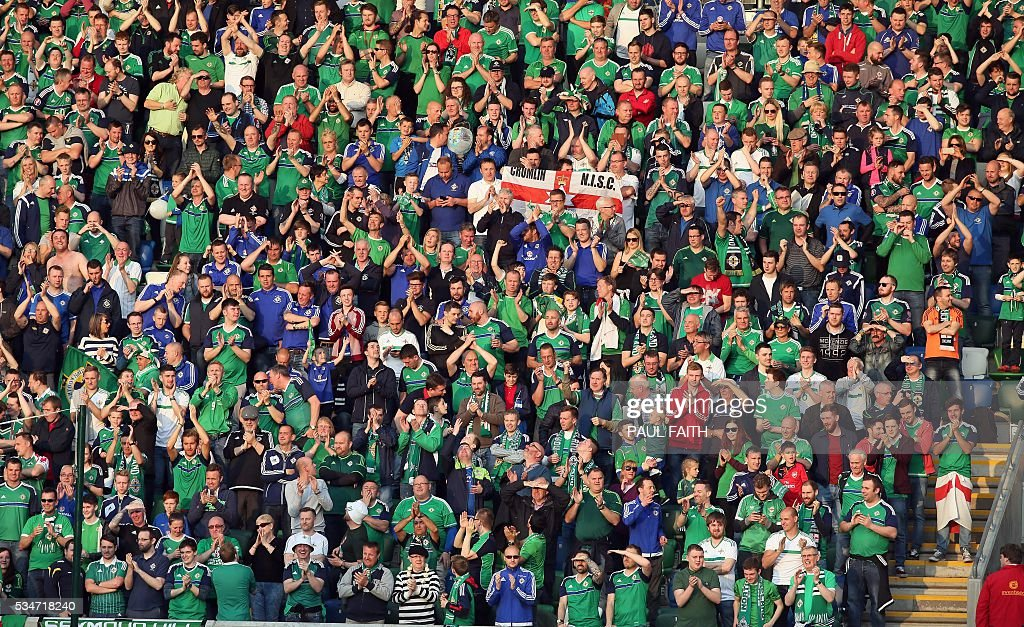 Northern Ireland's fans celebrate the second goal against Belarus during an international friendly football match between Northern Ireland and Belarus at Windsor Park in Belfast, Northern Ireland, on May 27, 2016. / AFP / PAUL