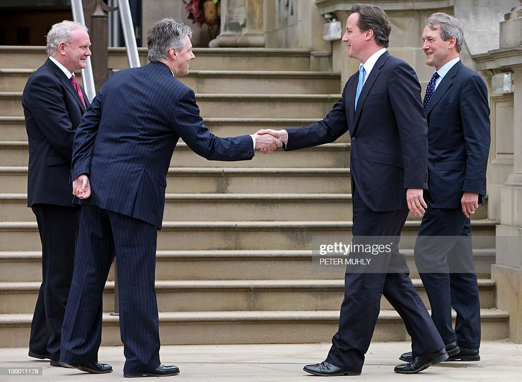 Northern Ireland's First Minister, Peter Robinson (2nd L), and Deputy First Minister, Martin McGuinness (L), greet British Prime Minister David Cameron (2nd R) and Northern Ireland Secretary, Owen Paterson, at Stormont Castle in Belfast, Northern Ireland May 20, 2010. Cameron and his coalition deputy unveiled full details Thursday of their 'historic' power-sharing deal, under growing scrutiny for signs of strain. AFP PHOTO/Peter Muhly