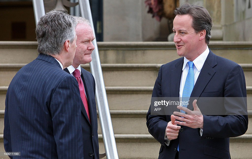 Northern Ireland's First Minister, Peter Robinson (L), and Deputy First Minister, Martin McGuinness (2nd L), greet British Prime Minister David Cameron and Northern Ireland Secretary, Owen Paterson (not pictured), at Stormont Castle in Belfast, Northern Ireland May 20, 2010. Cameron and his coalition deputy unveiled full details Thursday of their 'historic' power-sharing deal, under growing scrutiny for signs of strain. AFP PHOTO/Peter Muhly