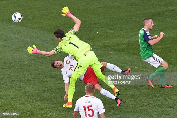 TOPSHOT Northern Ireland's goalkeeper Michael McGovern collides with Poland's defender Lukasz Piszczek during the Euro 2016 group C football match...