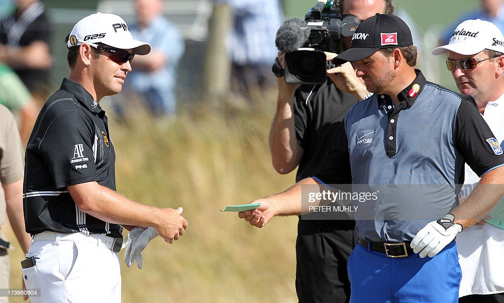 Northern Ireland's Graeme McDowell (R) gives the score card to South Africa's Louis Oosthuizen as the latter withdraws from competition during the first round of the 2013 British Open Golf Championship at Muirfield golf course at Gullane in Scotland on July 18, 2013. Oosthuizen withdrew from the British Open after nine holes of the first round at Muirfield with what appeared to be a leg injury.