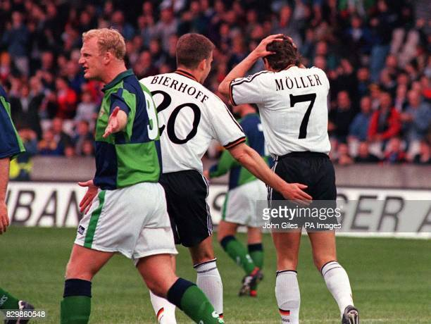Northern Ireland's Iain Dowie argues a point as Andreas Moller of Germany is consoled by Oliver Bierhoff after he missed a penalty the second penalty...