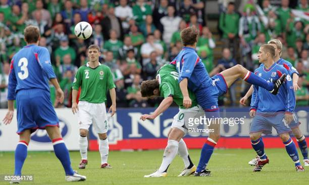Northern Ireland's James Quinn topples over Iceland's Hermes Thorstein Sigurdsson during the European Championship qualifying match at Windsor Park...