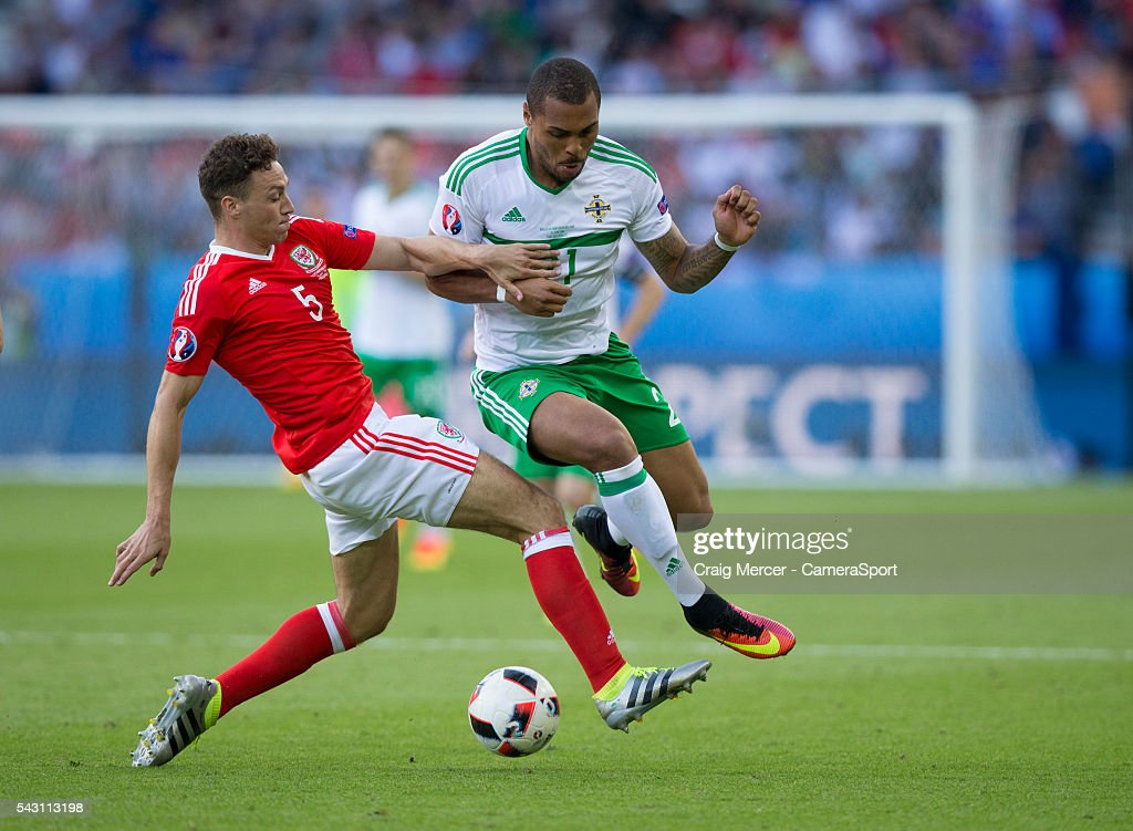 Northern Ireland's Josh Magennis rides the tackle of Wales's James Chester during the UEFA Euro 2016 Round of 16 match between Wales and Northern Ireland at Parc des Princes on June 25 in Paris, France.
