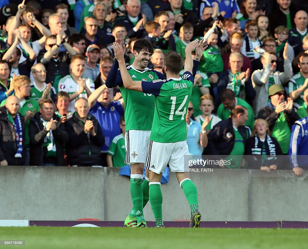 Northern Ireland's Kyle Laverty (10) celebrates with Stuart Dallas after scoring against Belarus during an international friendly football match between Northern Ireland and Belarus at Windsor Park in Belfast, Northern Ireland, on May 27, 2016. / AFP / PAUL