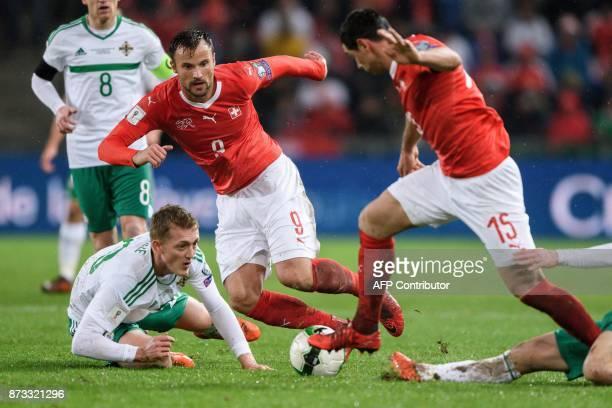 Northern Ireland's midfielder George Saville Swiss foward Haris Seferovic and Swiss midfielder Blerim Dzemaili vie for the ball during the FIFA 2018...