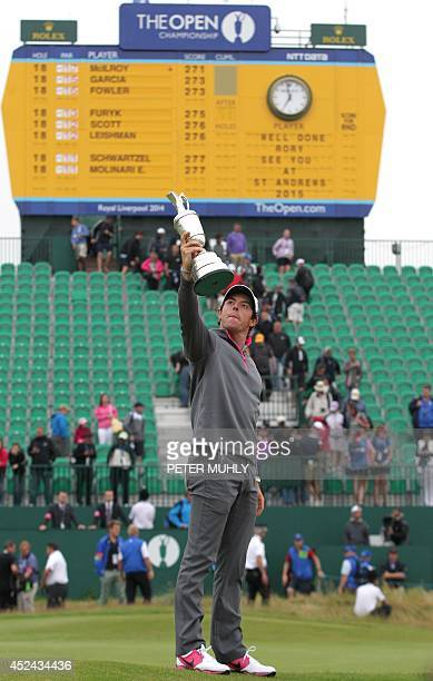 Northern Ireland's Rory McIlroy holds up the Claret Jug in front of the scoreboard after winning the 2014 British Open Golf Championship at Royal...