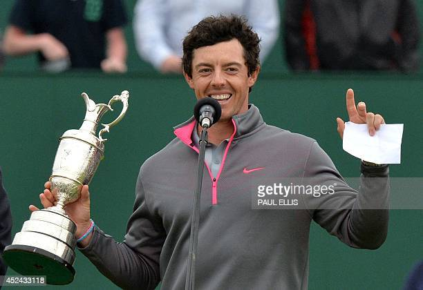Northern Ireland's Rory McIlroy jokes about being a supporter of Manchester United during a speech as he holds the Claret Jug after winning the 2014...