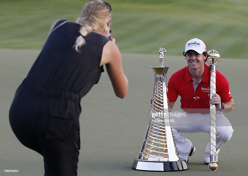 Northern Ireland's Rory McIlroy poses for his girlfriend, Denmark's tennis champion Caroline Wozniacki, after winning the DP World Tour golf Championship in the Gulf emirate of Dubai on November 25, 2012. McIlroy responded in magnificent fashion to Justin Rose's course record round of 10-under par 62 by making five birdies in his last five holes to win the Championships.