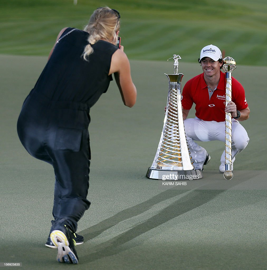 Northern Ireland's Rory McIlroy poses for his girlfriend, Denmark's tennis champion Caroline Wozniacki, after winning the DP World Tour golf Championship in the Gulf emirate of Dubai on November 25, 2012. McIlroy responded in magnificent fashion to Justin Rose's course record round of 10-under par 62 by making five birdies in his last five holes to win the Championships. AFP PHOTO / KARIM SAHIB